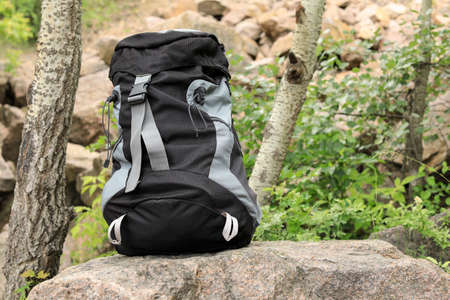 Large camping backpack on stone in forest. Space for text