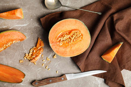 Flat lay composition with ripe cantaloupe melon on beige marble table