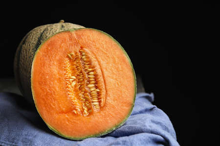 Tasty ripe cantaloupe melons on napkin against black background