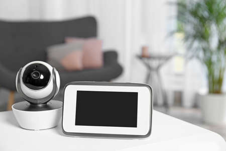 Baby monitor and camera on table in living room. Video nanny