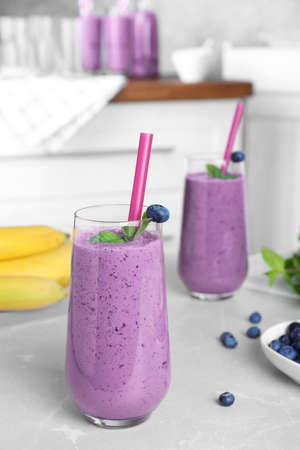 Glasses of delicious blueberry smoothie on light marble table in kitchen