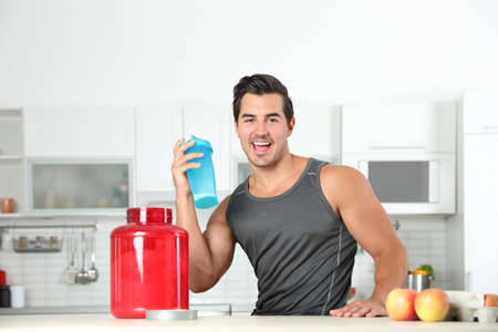 Young athletic man with ingredients for protein shake in kitchen