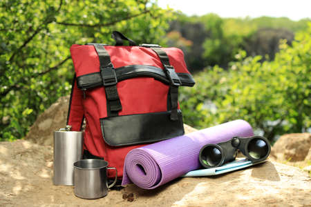 Modern backpack and camping equipment on large rock in wilderness