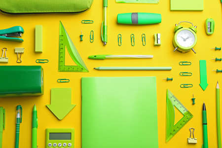Green school stationery on yellow background, flat lay Stockfoto