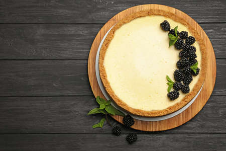 Delicious cheesecake decorated with blackberries on wooden table, flat lay. Space for text Stockfoto - 128779276