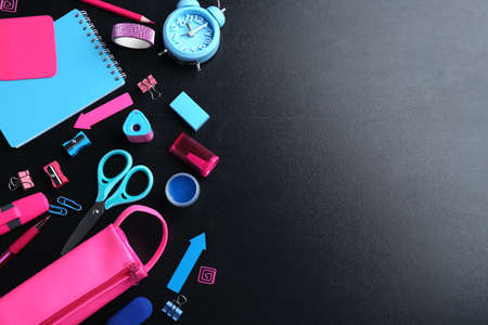 Different bright school stationery on black background, flat lay. Space for text Фото со стока
