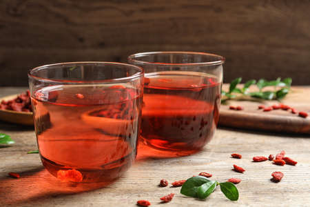 Healthy goji juice in glasses on wooden table