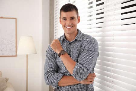 Portrait of handsome young man near window blinds indoors Banco de Imagens