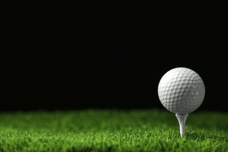 Golf ball with tee on artificial grass against black background, space for text Banco de Imagens