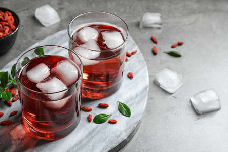 Healthy goji juice with ice in glasses on grey table. Space or text