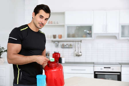 Young athletic man preparing protein shake in kitchen, space for text