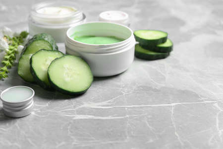 Jars of body cream and cucumber slices on grey marble background. Space for text
