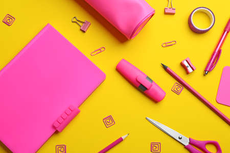 Pink school stationery on yellow background, flat lay