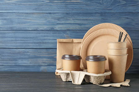 New paper dishware on table against blue wooden background, space for text. Eco life