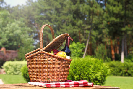 Picnic basket with fruits, bottle of wine and checkered blanket on wooden table in garden. Space for text