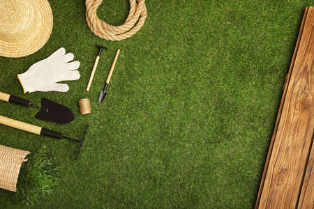 Set of gardening tools on green grass, flat lay. Space for text