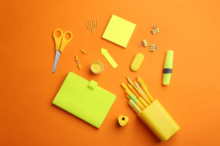 Different bright school stationery on orange background, flat lay