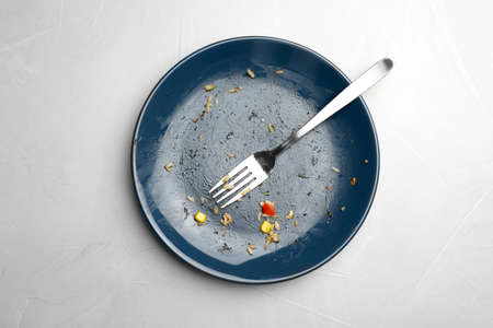 Dirty plate with food leftovers and fork on grey background, top view Imagens