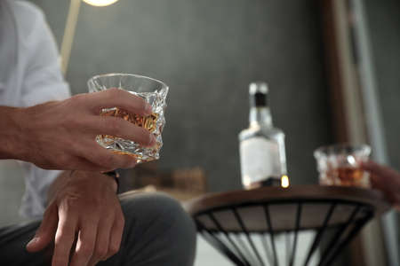 Man with glass of whiskey indoors, closeup view. Space for text