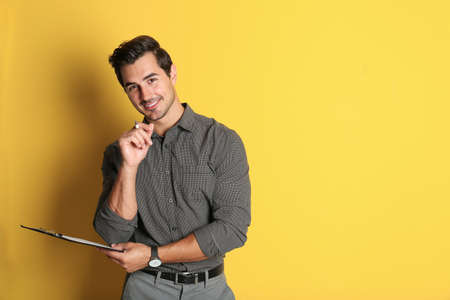 Young male teacher with clipboard on yellow background. Space for text Stock Photo - 129024643