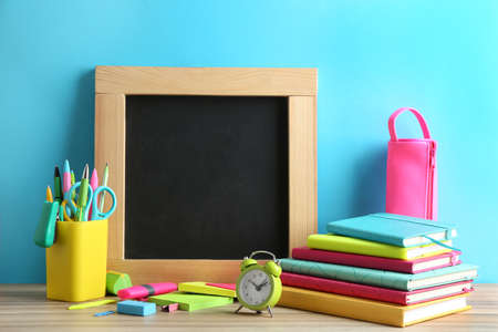 Different school stationery and small blank chalkboard on table near light blue wall. Space for text