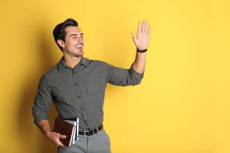 Young male teacher with books on yellow background. Space for text Stock Photo - 129024649