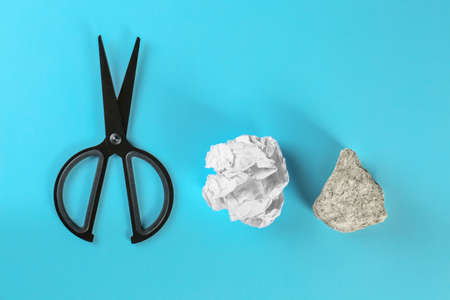Flat lay composition with rock, paper and scissors on light blue background