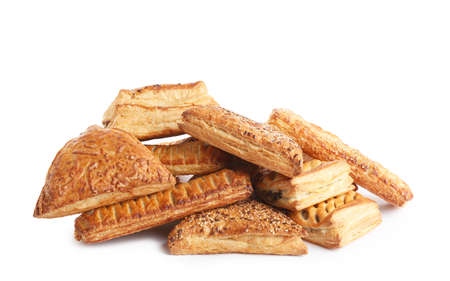 Heap of fresh tasty puff pastries on white background