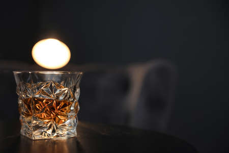 Glass of whiskey on table against dark background. Space for text
