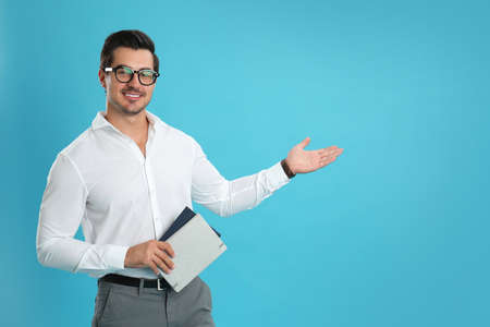 Young male teacher with glasses and notebooks on light blue background. Space for text Stock Photo - 129027589