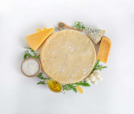Composition with pizza crust and fresh ingredients on white background, top view
