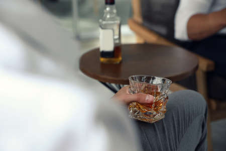 Man with glass of whiskey indoors, closeup view. Space for text Stockfoto - 128780681