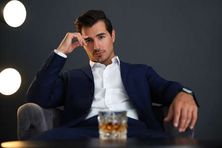 Young man with glass of whiskey indoors