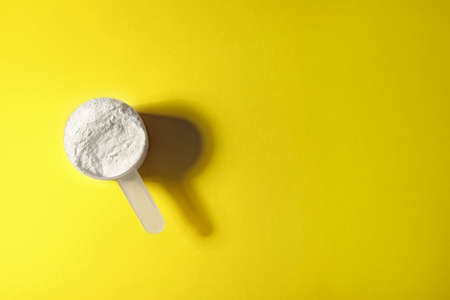 Scoop of protein powder on yellow background, top view with space for text