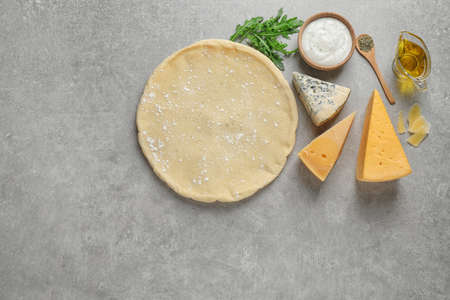 Flat lay composition with pizza crust and fresh ingredients on grey table. Space for text