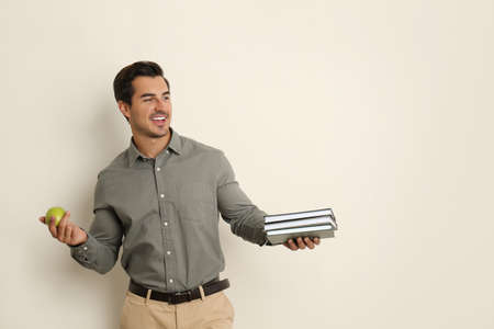 Young male teacher with books and apple on beige background. Space for text Stock Photo