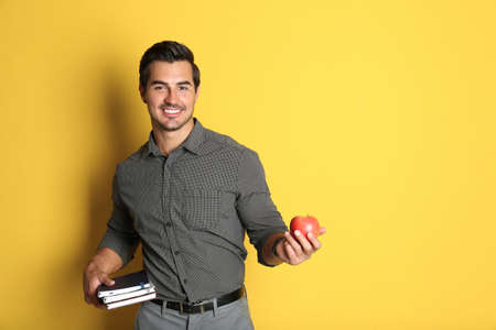 Young male teacher with books and apple on yellow background. Space for text Stock Photo