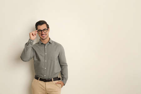Young man with glasses on beige background. Space for text Stock Photo - 129028981