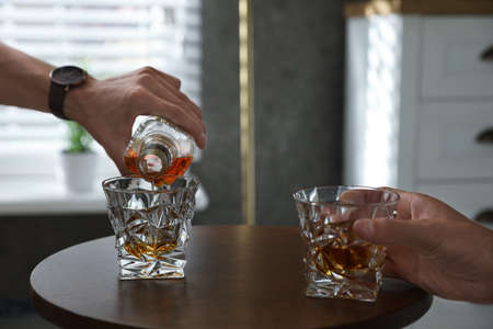 Young men drinking whiskey together at home, closeup