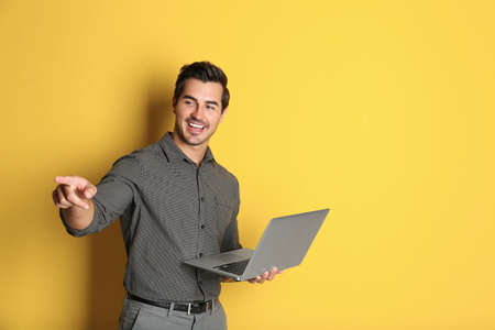 Young male teacher with laptop on yellow background. Space for text Stock Photo