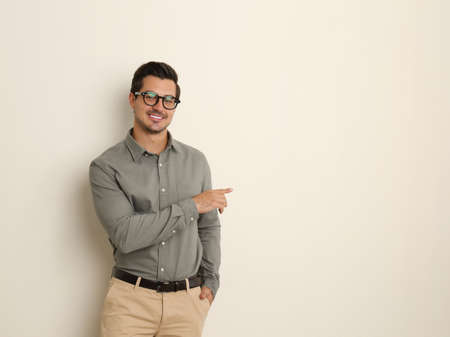 Young male teacher with glasses on beige background. Space for text Stock Photo - 129028995