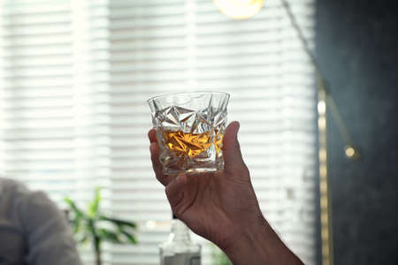Man with glass of whiskey indoors, closeup view Stockfoto - 128780249