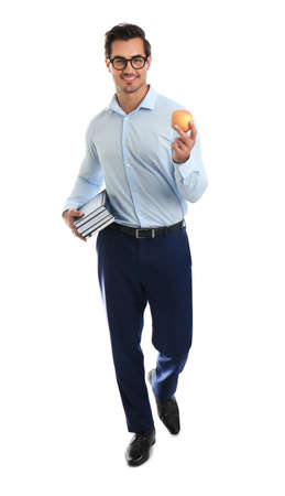 Young male teacher with books and apple on white background