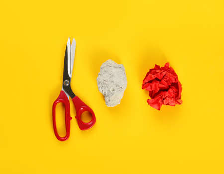 Flat lay composition with rock, paper and scissors on yellow background Zdjęcie Seryjne