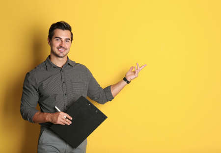 Young male teacher with clipboard on yellow background. Space for text