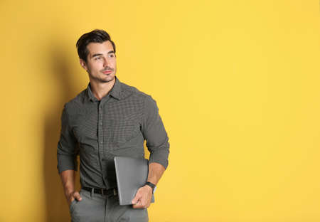Young male teacher with laptop on yellow background. Space for text Foto de archivo