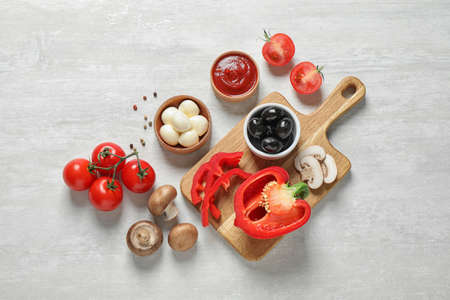 Flat lay composition with fresh ingredients for pizza on white wooden table