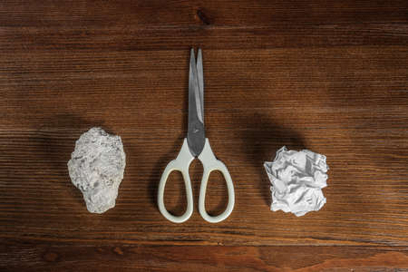 Flat lay composition with rock, paper and scissors on wooden background Standard-Bild