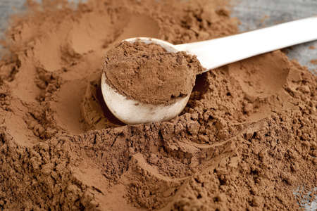 Pile of chocolate protein powder and scoop on grey table, closeup