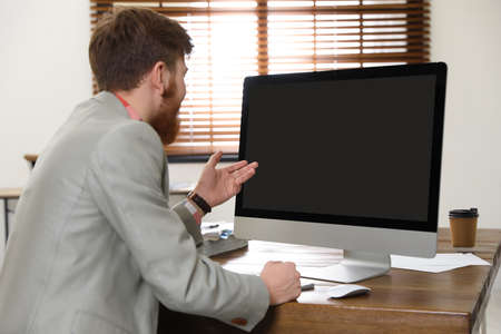 Man using video chat on computer in home office. Space for text